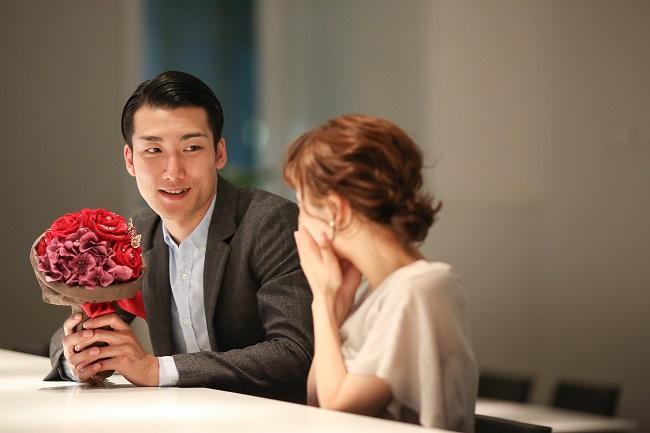 赤バラの花束をプレゼントする男性